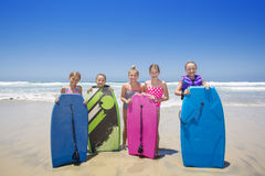 Kids playing at the beach together while on vacation. A cute group of kids standing by a boogie boards at the beach while playing in the ocean on vacation. Lots Royalty Free Stock Photo