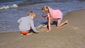 Kids playing at the beach. Two kids playing at the beach stock footage