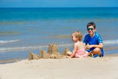 Kids playing on a beach. Two children build a sand castle at the sea shore. Family vacation on a tropical resort. Traveling with royalty free stock photography