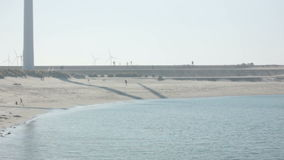 Kids playing at the Beach under Turbine Windmills. Static medium long shot during a hazy sunny day of a sandy beach surrounded midst a turbine windmill park stock footage