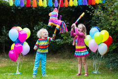 Kids playing with birthday pinata. Kids birthday party. Group of children hitting pinata and playing with balloons. Family and friends celebrating birthday Stock Images