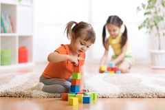 Kids playing block toys in playroom at nursery Royalty Free Stock Photo