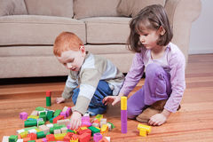 Kids playing with blocks. Two kids playing with blocks in front of couch Royalty Free Stock Photography
