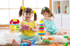 Kids playing with blocks together. Educational toys for preschool and kindergarten child. Little girls build toys at stock images