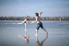 Kids Playing on blue sky beach Stock Image