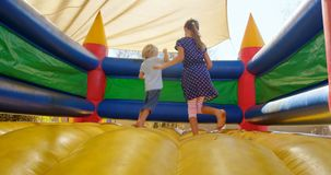 Kids playing on the bouncing castle 4k. Kids playing on the bouncing castle in the playground 4k stock video