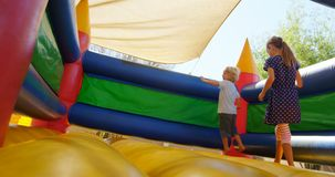 Kids playing on the bouncing castle 4k. Kids playing on the bouncing castle in the playground 4k stock footage