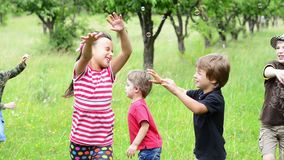 Kids Playing with Bubbles. Parent playing with kids with a bubble blower in a orchard stock footage