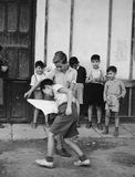 Kids playing bullfighting game in street. (All persons depicted are no longer living and no estate exists. Supplier grants that there will be no model release royalty free stock photo