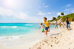Kids playing catch-up on sandy beach Stock Images
