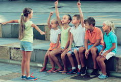 Kids playing charades outdoors. Kids in school age playing charades outdoors Stock Images