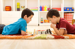 Kids playing chess. Serious kids playing chess laying on the floor in their room Royalty Free Stock Photos