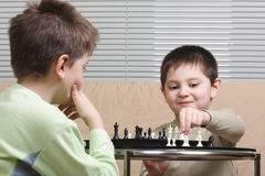 Kids playing chess. Two kids playing chess sitting on brown sofa Stock Photography