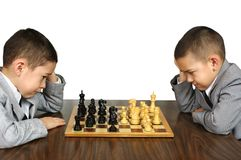 Kids playing chess. Two boys, aged six and eight years, think seriously while playing a game of chess Stock Image