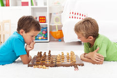 Kids playing chess. Laying on the floor and thinking intensely Stock Photography