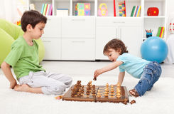 Kids playing chess. Small kids playing chess in their room Stock Image