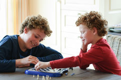 Kids playing Chess. Two boys playing chess at the kitchen table and having fun together Stock Images