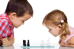 Kids playing chess. Serious kids playing chess - isolated royalty free stock photo