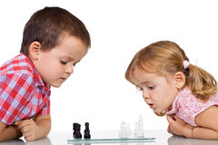 Kids playing chess. Concentrated kids playing chess - isolated stock photo