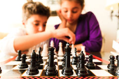 Kids playing Chess. Brother and sister playing chess Royalty Free Stock Photography
