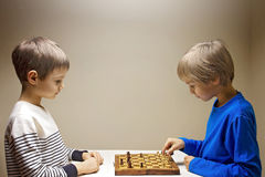 Kids playing chess. Kids playing a game of chess. Game, education, lifestyle concept Stock Photos