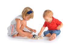 Kids playing chess. Girl and little boy playing chess isolated over white background Royalty Free Stock Images