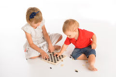 Kids playing chess. Girl and little boy playing chess  over white background Stock Photo