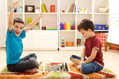 Kids playing chess - just captured a pawn. Kids playing chess - one of them just captured a pawn and celebrates Stock Photos
