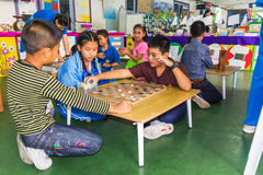 Kids playing chess. MUEANG, CHIANG MAI, THAILAND-FEBRUARY 09 : Kids playing chess laying on the floor and thinking intensely in Academic Day 2015 Kowitthamrong Royalty Free Stock Photos