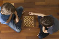 Kids playing chess sitting on wooden floor. Top view. Game, education, lifestyle, leisure concept. Kids playing chess sitting on wooden floor. Top view Royalty Free Stock Images