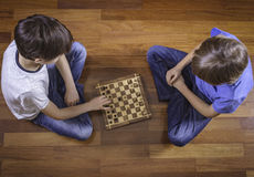 Kids playing chess sitting on wooden floor. Top view. Game, education, lifestyle, leisure concept. Kids playing chess sitting on wooden floor. Game, education Royalty Free Stock Photo