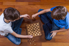 Kids playing chess sitting on wooden floor. Top view. Game, education, lifestyle, leisure concept. Kids playing chess sitting on wooden floor. Game, education Stock Images