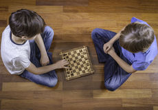 Kids playing chess sitting on wooden floor. Top view. Game, education, lifestyle, leisure concept. Kids playing chess sitting on wooden floor. Game, education Stock Image