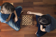 Kids playing chess sitting on wooden floor. Top view. Game, education, lifestyle, leisure concept. Toned image Stock Photo