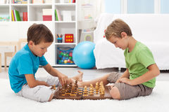 Kids playing chess in their room. Kids playing chess sitting on the floor in their room Stock Photo