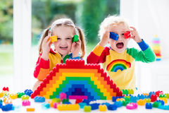 Kids playing with colorful blocks. Child playing with colorful toys. Little girl and funny curly baby boy with educational toy blocks. Children play at day care Royalty Free Stock Image