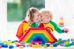 Kids playing with colorful blocks. Child playing with colorful toys. Little girl and funny curly baby boy with educational toy blocks. Children play at day care Stock Photos