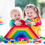 Kids playing with colorful blocks. Child playing with colorful toys. Little girl and funny curly baby boy with educational toy blocks. Children play at day care Stock Photography