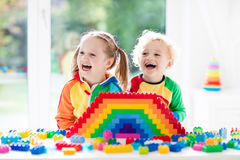 Kids playing with colorful blocks. Child playing with colorful toys. Little girl and funny curly baby boy with educational toy blocks. Children play at day care Stock Photo