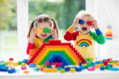 Kids playing with colorful blocks. Child playing with colorful toys. Little girl and funny curly baby boy with educational toy blocks. Children play at day care Stock Images