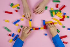 Kids playing with colorful building plastic bricks on pink background. Educational developing toys background stock image