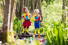 Kids playing with colorful paper boats in a park. Children play with colorful paper boats in a small river on a sunny spring day. Kids playing exploring the Royalty Free Stock Image