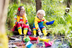 Kids playing with colorful paper boats in a park. Children play with colorful paper boats in a small river on a sunny spring day. Kids playing exploring the Royalty Free Stock Photo