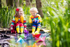 Kids playing with colorful paper boats in a park. Children play with colorful paper boats in a small river on a sunny spring day. Kids playing exploring the Stock Photography