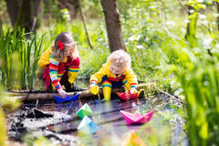 Kids playing with colorful paper boats in a park. Children play with colorful paper boats in a small river on a sunny spring day. Kids playing exploring the Royalty Free Stock Photos