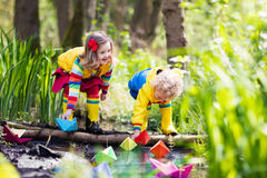 Kids playing with colorful paper boats in a park. Children play with colorful paper boats in a small river on a sunny spring day. Kids playing exploring the Royalty Free Stock Photography