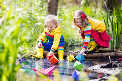 Kids playing with colorful paper boats in a park. Children play with colorful paper boats in a small river on a sunny spring day. Kids playing exploring the Royalty Free Stock Images