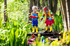 Kids playing with colorful paper boats in a park. Children play with colorful paper boats in a small river on a sunny spring day. Kids playing exploring the Stock Image