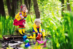 Kids playing with colorful paper boats in a park Stock Photos