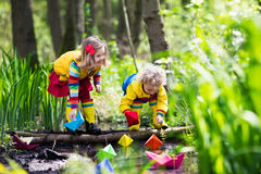 Kids playing with colorful paper boats in a park Royalty Free Stock Images